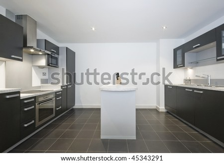 large luxury kitchen with separate work areas and isle - stock photo