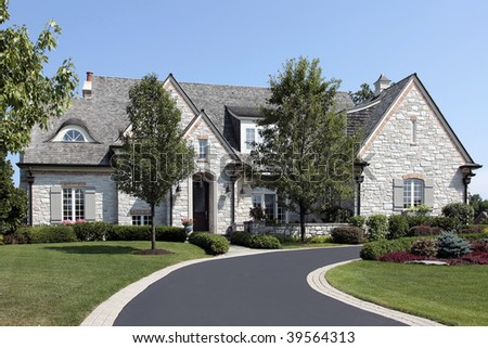 Large luxury stone home with circular driveway - stock photo