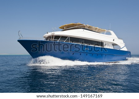 Large luxury wooden motor yacht traveling on a tropical sea