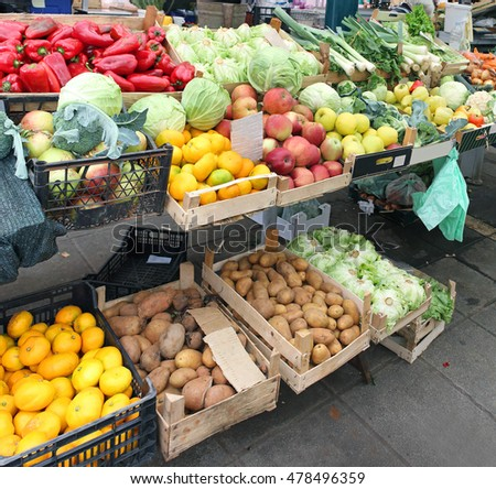 Large market stall with piles of fruits and vegetables