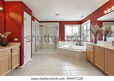 Large master bath with red walls and glass shower - stock photo