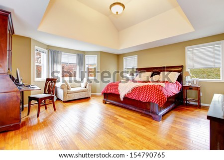 Large master bedroom interiors with vaulted ceiling and hardwood floors. - stock photo