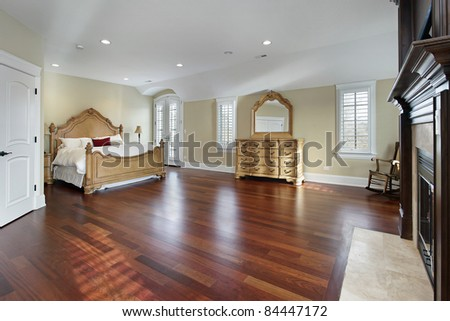 Large master bedroom with cherry wood flooring - stock photo