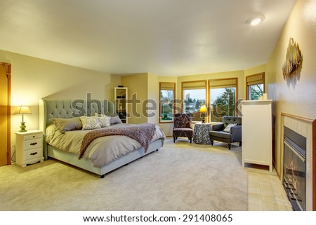 Large master bedroom with fireplace and bed. - stock photo