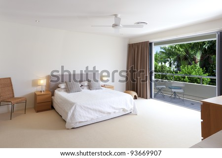 Large master bedroom with king size bed and balcony - stock photo