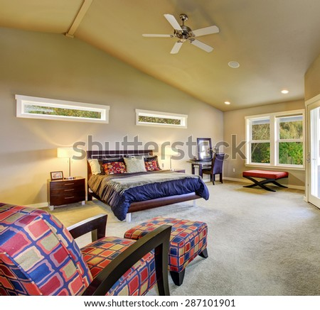 Large master bedroom with windows, fireplace, and colorful furniture. - stock photo