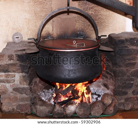 Large metal cauldron over a fire in a farm house used for boiling milk to make cheese in Switzerland. - stock photo