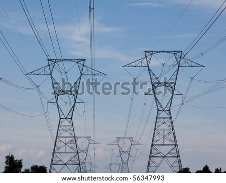 Large metal electricity pylons march across the countryside - stock photo