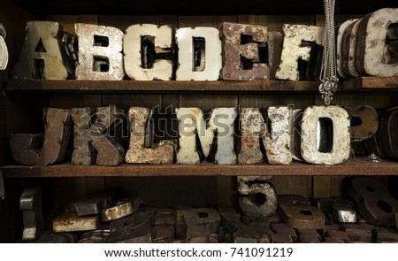 Large metal, rusted, typeface letters displayed on shelves