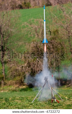 Large model rocket blasts off the pad with a long flame emitting from its thruster and plentiful smoke.