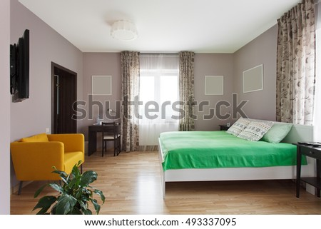 Large modern bedroom in green and yellow colors with small workplace