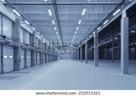 Large modern empty storehouse with blue tint - stock photo
