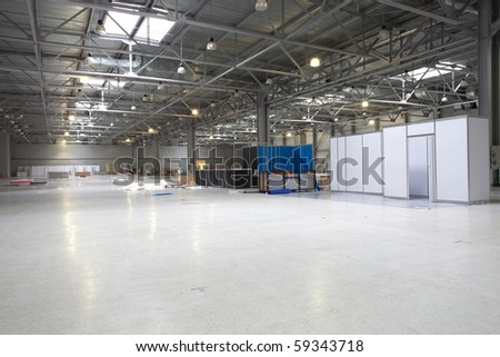 Large modern  exibition hall that unprepaired for exibition yet but already with some goods - stock photo