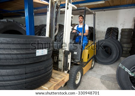 Large modern garage with forklifts and stack of car tires - stock photo