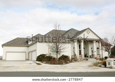 Large modern gray house under cloudy sky - stock photo