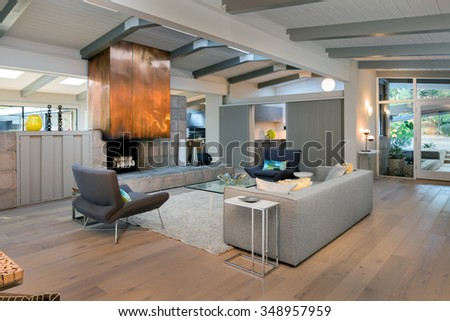 Large Modern living room interior in mid century home with couch, fire place, hand-woven rug, glass table, designer chairs in open space. - stock photo