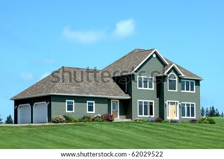 Large modern style residential home with very large front yard. - stock photo