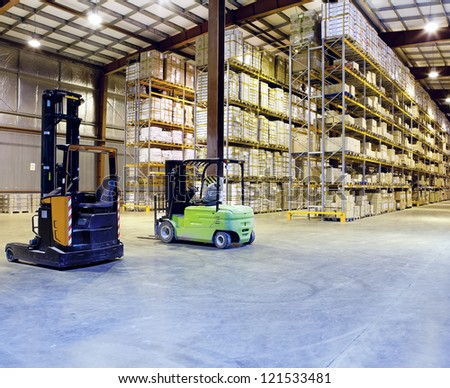 Large modern warehouse with forklifts - stock photo