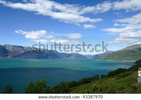 large mountain lake with snowed mountains in the background, norway - stock photo