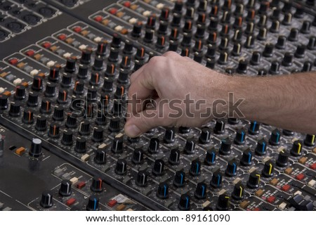 Large Music Mixer desk in the music studio with the operator's hand