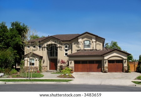 Large, new home with 3-car garage against blue sky - stock photo