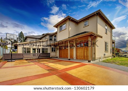 Large New luxury home exterior with orange and red driveway. - stock photo