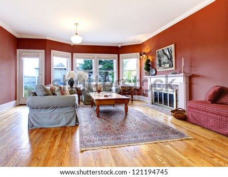 Large nice living room with red walls and fireplace. - stock photo