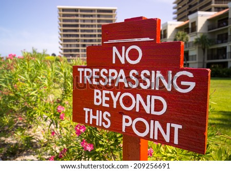 Large no trespassing sign in front of flower gardens in holiday resort or private apartments by beach in Florida - stock photo