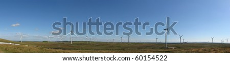 Large number of modern wind turbines on a wind farm in Scotland, UK, Europe. Panorama taking in around 180 degrees.