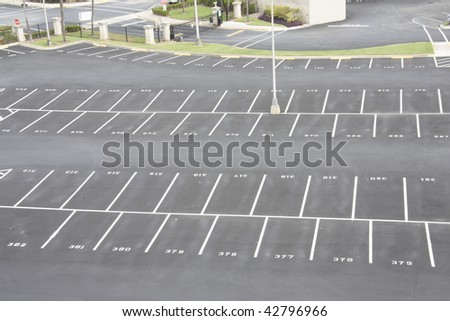 large, numbered, empty parking lot with offset spaces - stock photo