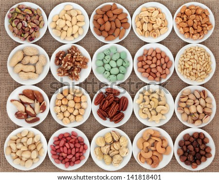 Large nut selection in white porcelain bowls over hessian background. - stock photo
