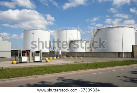 Large oil silo's and pumps along the road in Rotterdam harbor area