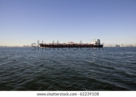 Large oil tanker anchored in a wide industrial harbor.
