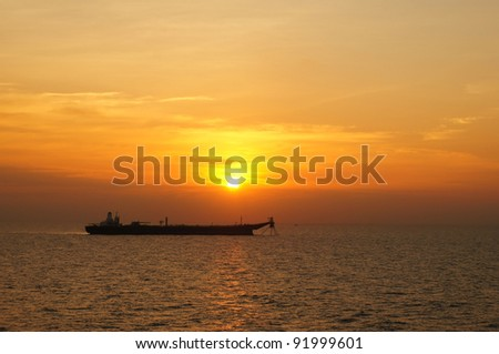 Large oil tanker anchored in the middle of sea in the evening - stock photo