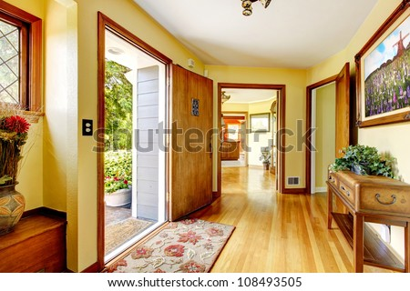 Large old luxury house entrance interior with art and yellow walls. - stock photo