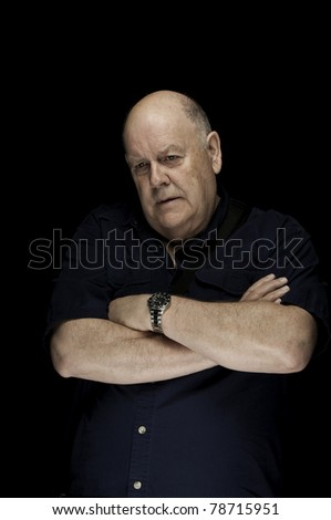 Large older man looking down. He has very little hair on his head - stock photo