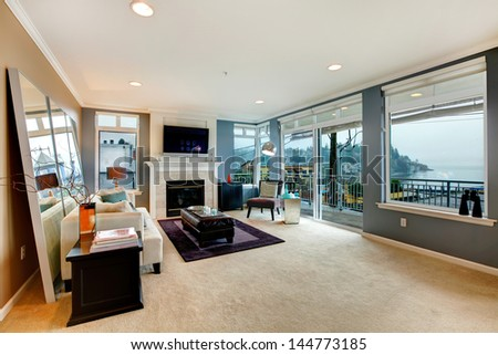 Large open bight living room with fireplace, TV and modern furniture. - stock photo
