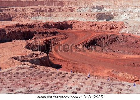 Large, open-pit iron ore mine showing the various layers of soil and iron rich ore - stock photo