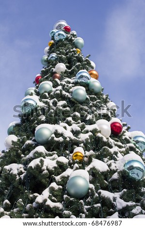 Large outdoor Christmas Tree decorated with balls and covered with snow - stock photo