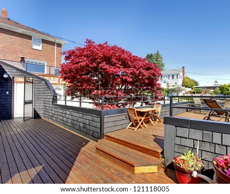 Large outdoor terrace with furniture in the front of the house. - stock photo