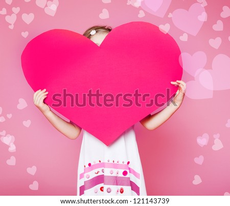 Large paper heart in hands of a little girl - stock photo