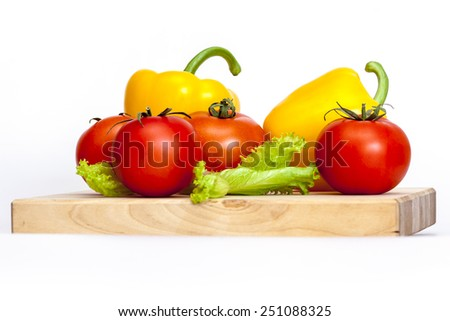 Large paprika of yellow color and red tomatoes - stock photo