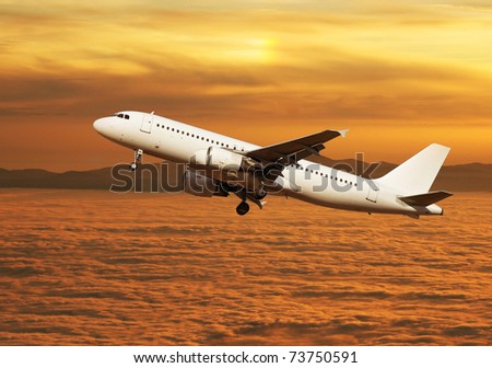 Large passenger plane flying over clouds at sunset - stock photo