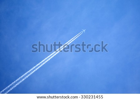 Large passenger supersonic plane flying high in blue sky with haze, leaving long white trace - stock photo
