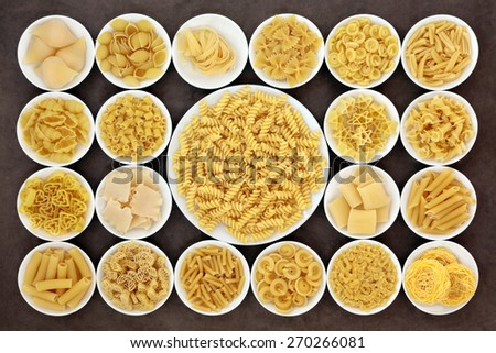 Large pasta dried food selection in round bowls over brown background. - stock photo