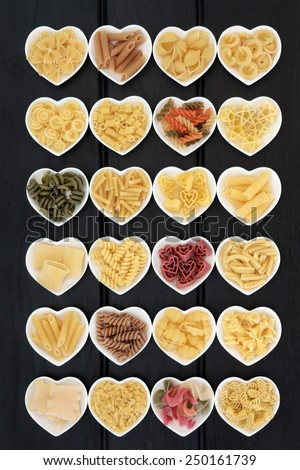 Large pasta food selection in heart shaped porcelain dishes over dark wood background. - stock photo