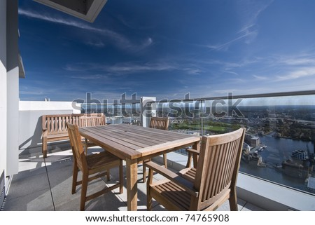Large penthouse terrace with dining table and chairs with city views