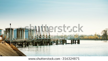Large petroleum export terminal on a river. Detailed refinery with pumps waiting for big tankers to load or unload crude oil - stock photo