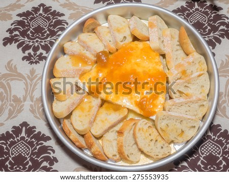Large piece of brie cheese topped with jam and served with sliced bread. - stock photo