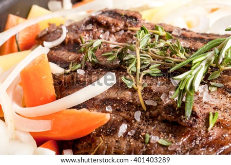 Large piece of fresh beef meat prepared on a grill pan with herbs and vegetables. Shallow depth of field. Toned. - stock photo